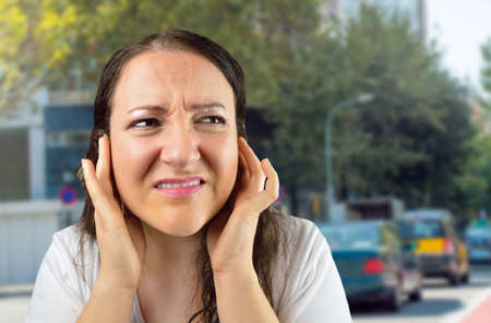 woman covering her ears with her hands at city Stock Photo
