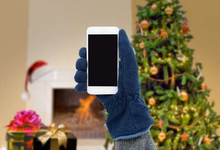 closeup of man with gloves using the smart phone with a Christmas tree background at home