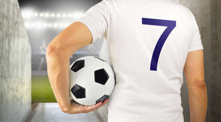 Cropped rearview image of a young player man holding a soccer ball under his arms at the stadium at arena tunnel