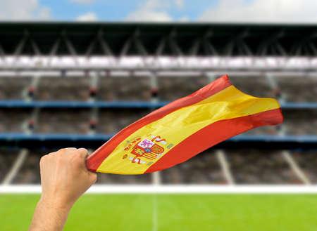 Spanish fan holding the flag of Spain at stadium.International soccer event
