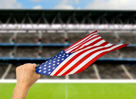American fan holding the flag of USA at stadium.International soccer event