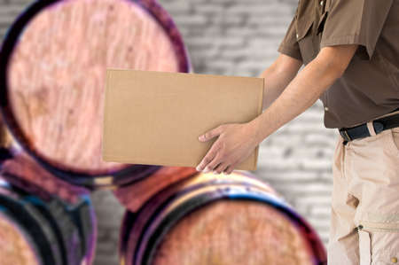 Man holding cardboard box of wine bottles at wine cellar