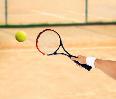 hand holding a tennis racket hitting a ball on a clay court Stock Photo