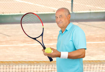 Smiling senior man standing and holding his racquet tennis on a clay court