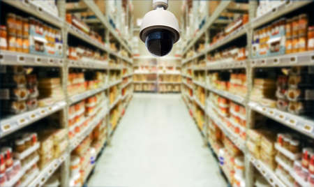 surveillance camera at an aisle of the warehouse as concept of the security system