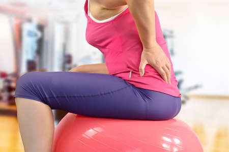 sportswoman practicing pilate with back pain sitting on the pilates ball at the gym
