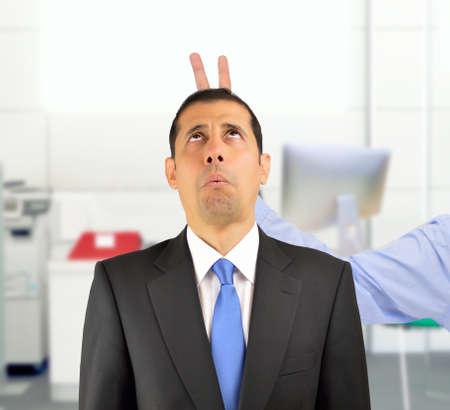 empresario tirando una broma de conejito dedos a su jefe en la oficina