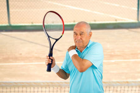 Shot of a tennis player with a shoulder injury on a clay court Stock Photo