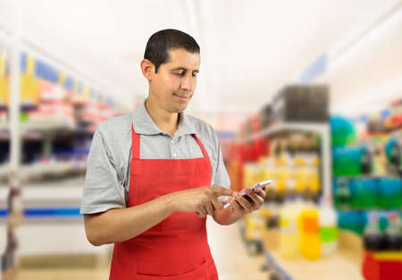 shopman with pinafore uses a smart phone at the supermarket