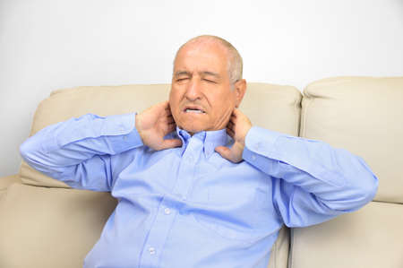 Senior man suffering neck pain sitting on a sofa in the living room at home