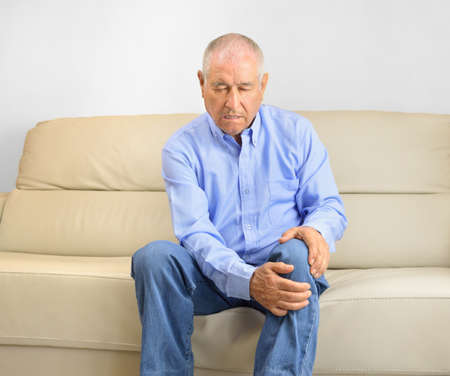 elderly man sitting on a sofa in the living room at home and touching his knee by the pain