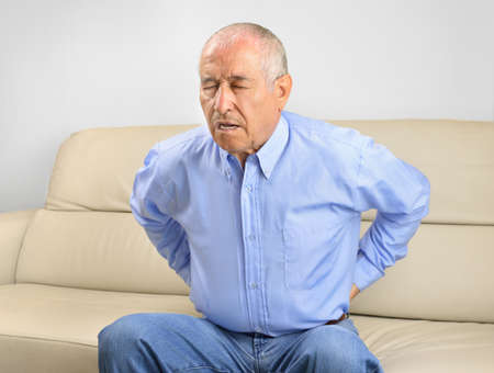 Unhappy senior man suffering back pain sitting on a sofa in the living room at home Stock Photo