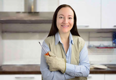 Portrait of a handyman woman smiling with screwdriver in hand and crossed arms at the kitchen