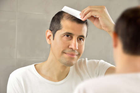 man holding a comb and combing in the bathroom gazing at you in the mirror