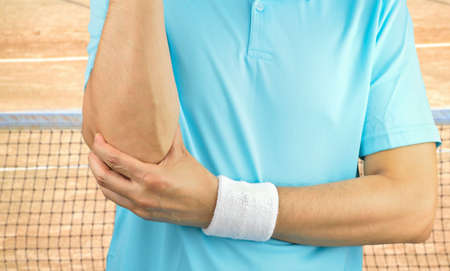 Shot of a tennis player with elbow injury on a clay court
