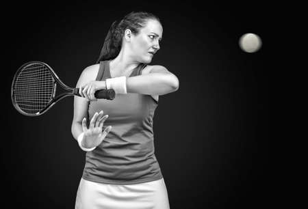 portrait of a  female tennis player standing hitting tthe ball on black background