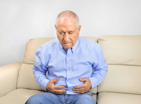 Senior man suffering stomach ache sitting on a couch in the living room at home Stock Photo