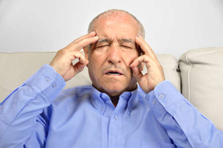 Senior man suffering headache and complaining sitting on a sofa in the living room of a house