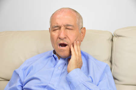 Toothache. Frustrated senior touching his cheek and keeping eyes closed while sitting on the couch at home Stock Photo