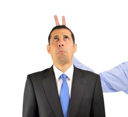 Empresario tirando una broma dedos conejito en su jefe aislado sobre fondo blanco. Foto de archivo