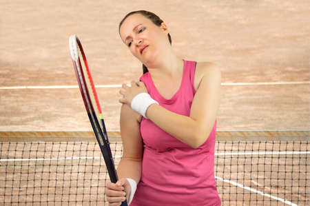 Shot of a tennis player with a shoulder injured on a clay court