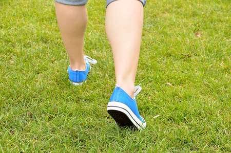 cropped back view of woman walking over the grass at the park with sneakers