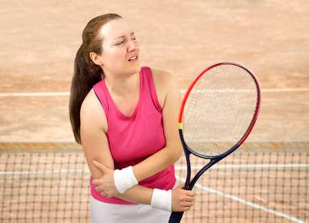 クレーコートでラケットを握る肘の怪我をしたテニス女子選手 写真素材