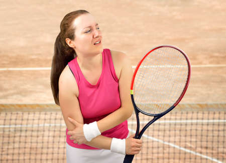tennis woman player with elbow injury holding the racket on a clay court Foto de archivo