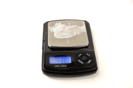 Cocaine powder on digital scales isolated on white background Stock Photo