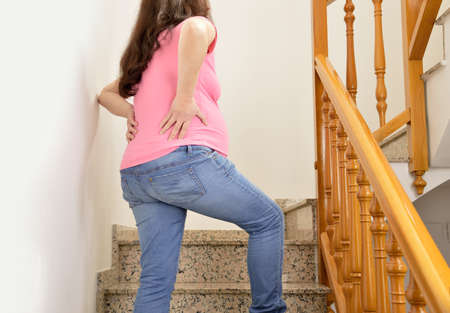detail of a pregnant woman  with backache because of falling on stairs of home