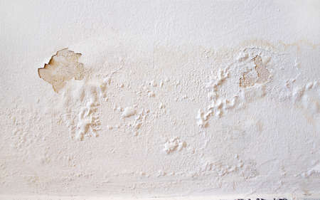 Rain water leaks on the wall causing damage and peeling paint  Stock Photo