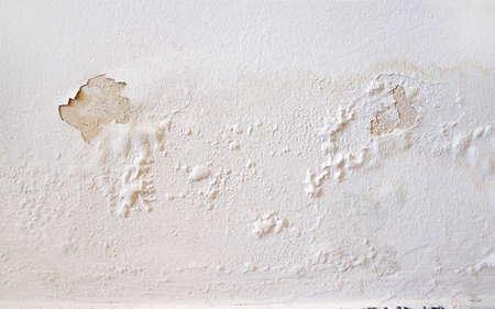 Regenwater lekt aan de muur en veroorzaakt schade en afbladderende verf
