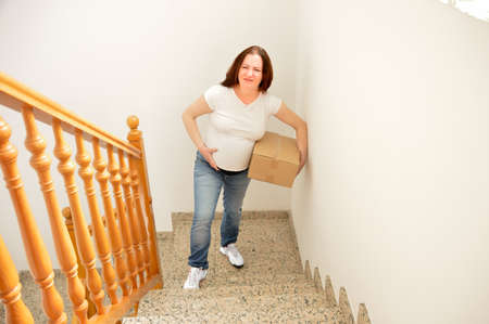 Pregnant woman climbing a box by some stairs