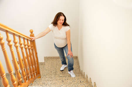 pregnant woman walking up the stairs at home and touching his knee by the pain