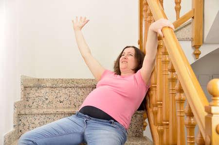 une femme enceinte tomber sur les escaliers avec les mains jusqu & # 39 ; à serrer le percer vers la balustrade