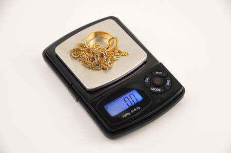 Jewelry on a scale in concept of the gold price Stockfoto