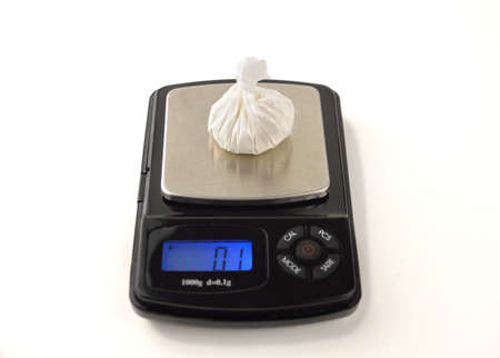 Cocaine bag on digital scales isolated on white background