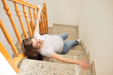 Pregnant woman falling down on stairs with hands up to try to catching the railing