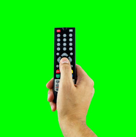 Hand holding television remote isolated cutout on green background with chroma key
