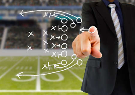 hand of a american football coach drawing a tactics of  football game  with white chalk on blackboard at arena stadium