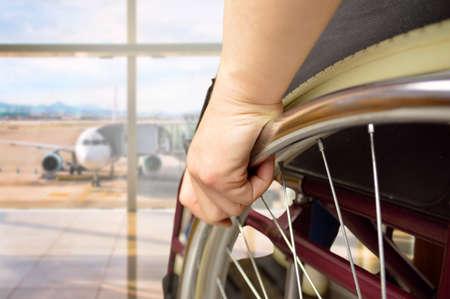 Vista trasera de un hombre en silla de ruedas en el aeropuerto con foco en mano Foto de archivo - 97246848
