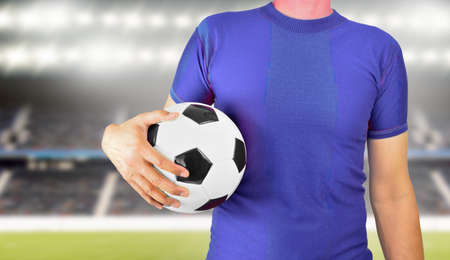 Cropped image of a young man holding a soccer ball with his hand wearing blue t-shirt at football stadium in background