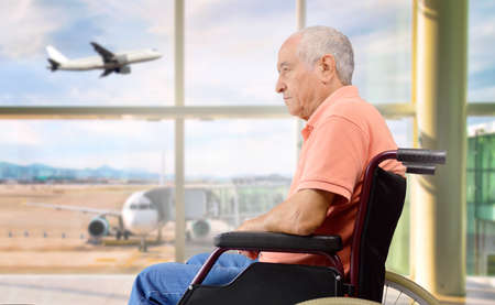 patient senior on a wheelchair at a airport looking outside