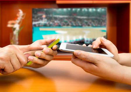 Freunde, die Handy verwenden und während eines Basketballspiels wetten. Mit einem Fernsehhintergrund und einem Bild eines Basketballspiels