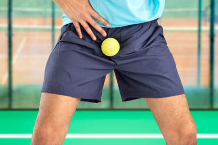 man playing paddle tennis being hit by a tennis ball with force in the crotch when he misses a catch or as an unexpected accident on a clay court