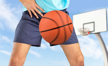 man playing basketball being hit by a basket ball with force in the crotch when he misses a catch or as an unexpected accident on a clay court
