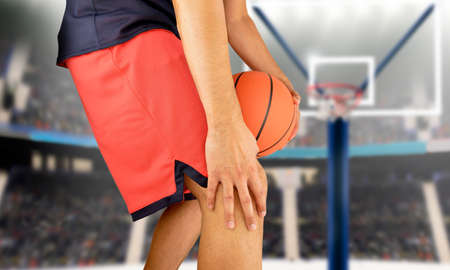 shot of a young basketball player with an inflamed knee at stadium Archivio Fotografico