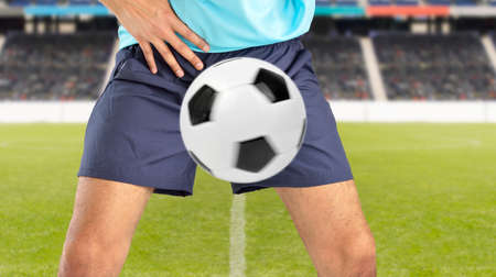 man playing soccer being hit by a soccer ball with force in the crotch when he misses a catch or as an unexpected accident on a clay court