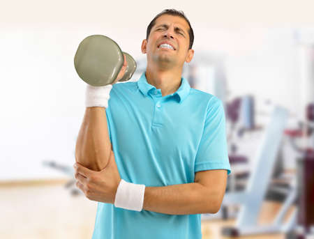 Shot of a young athlete with a elbow injury and working out using dumbbells Stok Fotoğraf