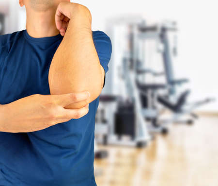 Shot of a young athlete with a elbow injury at gym